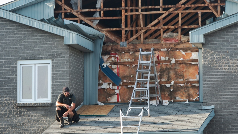 A man pauses as he repairs damage to his building after a tornado touched down in Mascouche, Que., northeast of Montreal, Monday, June 21, 2021. Dozens of homes were damaged and one death has been confirmed. THE CANADIAN PRESS/Ryan Remiorz