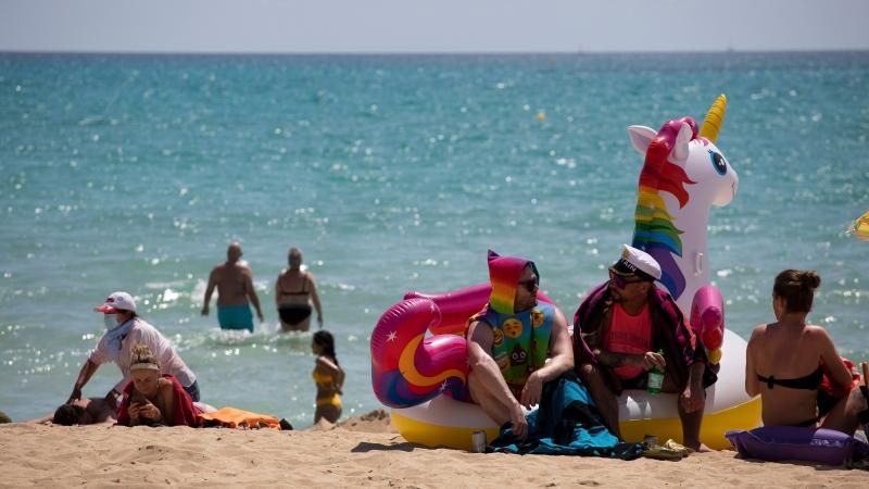 In this Monday, June 7, 2021 file photo, tourists sunbathe on the beach at the Spanish Balearic Island of Mallorca, Spain. (AP Photo/Francisco Ubilla, FIle)