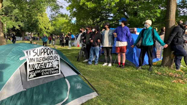 People are seen linking hands at an encampment at Trinity Bellwoods Park as city officials enforce trespass notices on Tuesday, June 22. (CTV News/Kenneth Enlow)