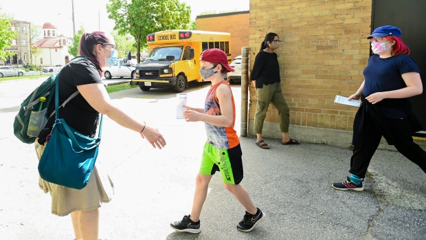 Jessica Lundeen, left, waits to hug her two kids Austin Lundeen, 12, centre, and Chantal Lundeen, 14, after receiving their COVID-19 Vaccine at Gordon A Brown Middle School in Toronto Wednesday May 19, 2021. THE CANADIAN PRESS/Nathan Denette