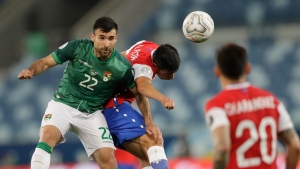 Bolivia's Danny Bejarano, left, and Chile's Tomas Alarcon head for the ball during a Copa America soccer match at Arena Pantanal stadium in Cuiaba, Brazil, Friday, June 18, 2021. (AP Photo/Andre Penner)