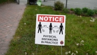 FILE - A physical distancing notice is seen at the Ottawa Tennis and Lawn Bowling Club in Ottawa, Friday, May 21, 2021, a day before tennis courts reopen as part of Ontario's phased reopening plan in the third wave of the COVID-19 pandemic. THE CANADIAN PRESS/Justin Tang