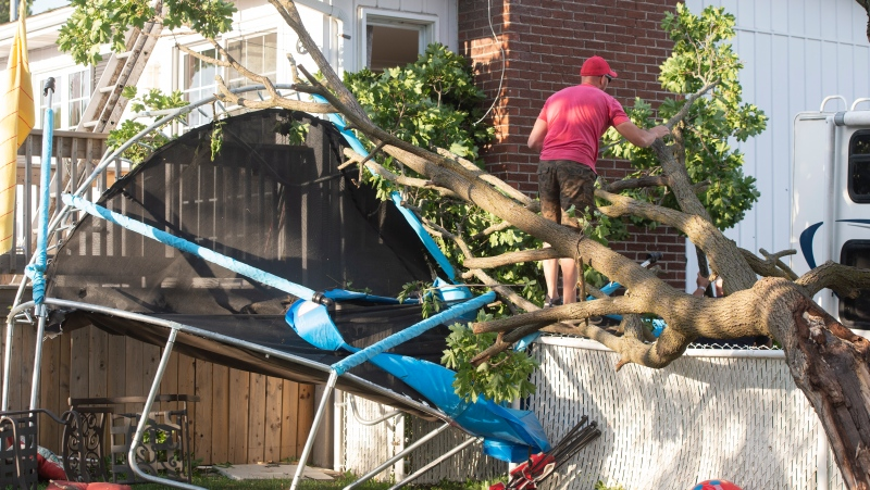 A man clears debris from his backyard after a tornado touched down in Mascouche, Que., northeast of Montreal, Monday, June 21, 2021. Dozens of homes were damaged and one death has been confirmed. THE CANADIAN PRESS/Ryan Remiorz