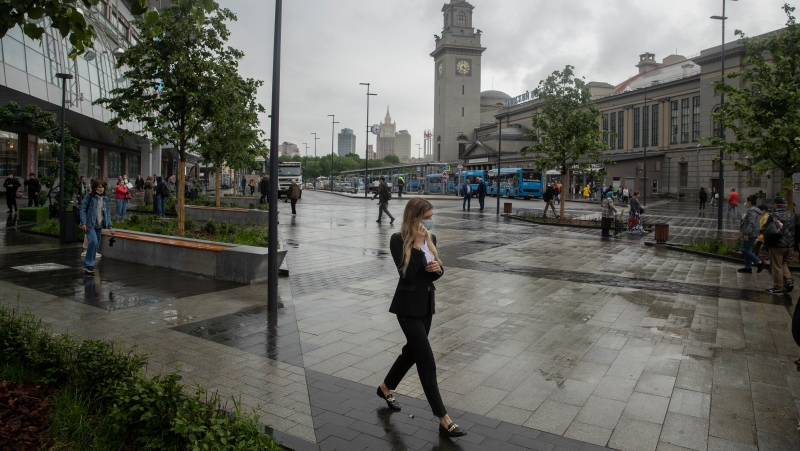 In this Thursday, July 10, 2021 file photo, a woman wearing a face walks in a street in Moscow, Russia. (AP Photo/Pavel Golovkin, file)