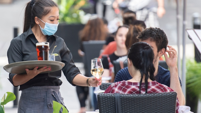 A server wears a face mask as she brings drinks to customers on a terrace in Old Montreal, Sunday, June 13, 2021, as the COVID-19 pandemic continues in Canada and around the world. THE CANADIAN PRESS/Graham Hughes