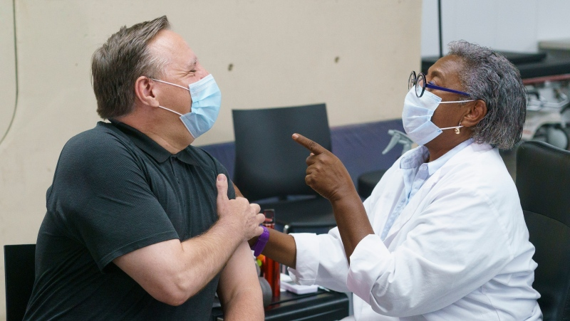 Quebec Premier Francois Legault jokes with Regine Laurent, after receiving his second dose of Pfizer vaccine at a COVID-19 vaccination clinic in Montreal, on Monday, June 21, 2021. THE CANADIAN PRESS/Paul Chiasson