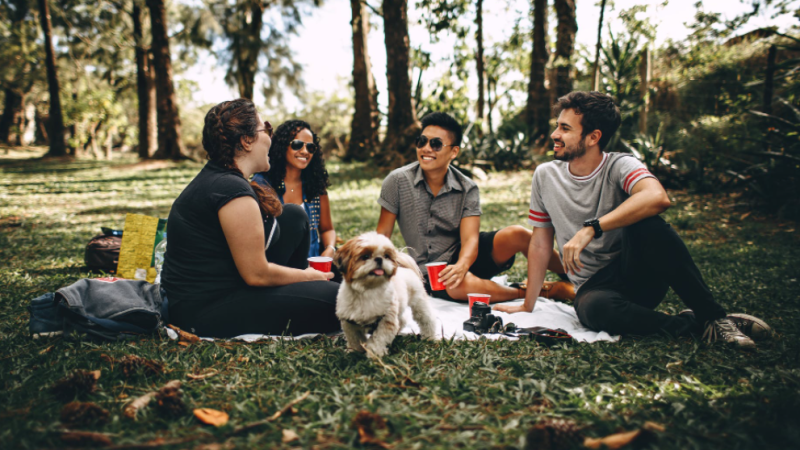 A group of friends hang out outside in this stock image. (Pexels)