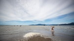A man rides a skimboard during low tide at Spanish Banks in Vancouver, B.C., Sunday, July 19, 2020. THE CANADIAN PRESS/Darryl Dyck