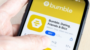 """A hand holds a smartphone with the Bumble dating icon on screen. The dating app has shut down its offices around the world the week of June 21 """"as a way to thank our team for their hard work and resilience,"""" it said. (Shutterstock via CNN)"""