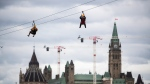 Parliament Hill is seen behind people riding the Interzip Rogers, billed as the world's first interprovincial zipline, connecting Ottawa and Gatineau over the Ottawa River, at its official opening event, in Ottawa, on Tuesday, June 22, 2021.  (Justin Tang/THE CANADIAN PRESS)