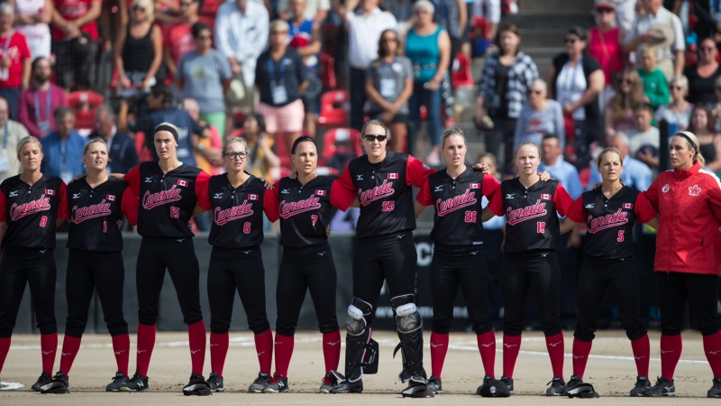 """Canada's Victoria Hayward, from left to right, Kelsey Jenkins, Jennifer Gilbert, Holly Speers, Jennifer Salling, Kaleigh Rafter, Larissa Franklin, Emma Entzminger, Joanne Lye and Danielle Lawrie stand during the playing of """"O Canada"""" before playing Brazil during playoff action at the Softball Americas Olympic Qualifier tournament in Surrey, B.C., on Sept. 1, 2019. THE CANADIAN PRESS/Darryl Dyck"""