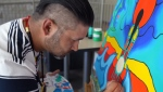 Ojibwe artist Mike Cywink works on a piece of his art.