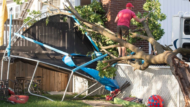 A man clears debris from his backyard after a tornado touched down in Mascouche, Que., northeast of Montreal, Monday, June 21, 2021. THE CANADIAN PRESS/Ryan Remiorz