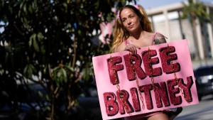 Britney Spears supporter Alandria Brown, of Hendersonville, Tenn., holds a sign outside a court hearing concerning the pop singer's conservatorship at the Stanley Mosk Courthouse, Thursday, Feb. 11, 2021, in Los Angeles. (AP Photo/Chris Pizzello)