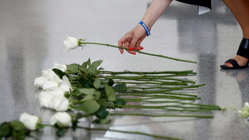 Andrea Chamblee, widow of Capital Gazette journalist John McNamara, places a flower at the foot of the Newseum's Journalists Memorial in Washington, Monday, June 3, 2019, during a rededication ceremony. (AP Photo/Patrick Semansky)