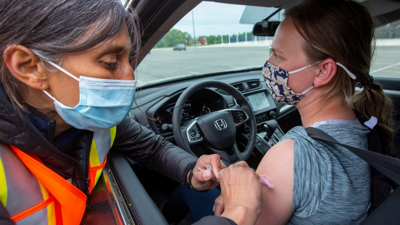 A person receives the Moderna vaccine from Dr. Rupa Patel during a COVID-19 vaccine clinic at Richardson Stadium in Kingston, Ont., on Friday, May 28, 2021. THE CANADIAN PRESS/Lars Hagberg