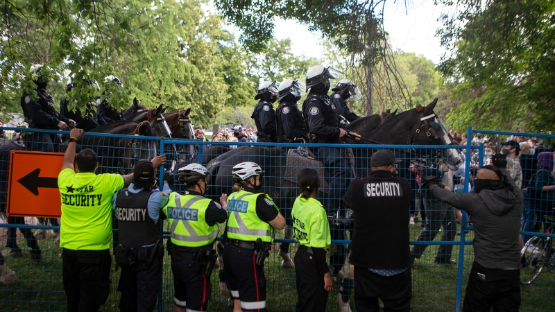 Mounted Police reinforce the perimeter of a fence after it was breached by supporters during an eviction process at a homeless encampment in Toronto, on Tuesday, June 22, 2021.THE CANADIAN PRESS/Chris Young