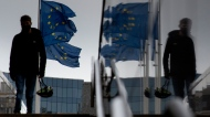 A man carries a cycling helmet as he walks by E.U. flags outside E.U. headquarters in Brussels, Wednesday, Oct. 28, 2020.
