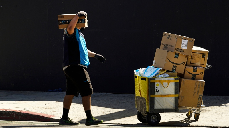 In this Thursday, Oct. 1, 2020, photo an Amazon worker wears a mask and gloves as he delivers boxes downtown Los Angeles. (AP Photo/Damian Dovarganes)