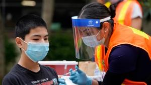 Noah Chen, 13, gets a shot of the Pfizer COVID-19 vaccine at the First Baptist Church of Pasadena, Friday, May 14, 2021, in Pasadena, Calif. (AP Photo/Marcio Jose Sanchez)