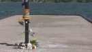An orange vest wrapped around a post along with some flowers are left in honour of a community volunteer who died after falling into the water at Couchiching Beach Park in Orillia, Ont./Wed. June 23, 2021 (Katelyn Wilson/CTV News)