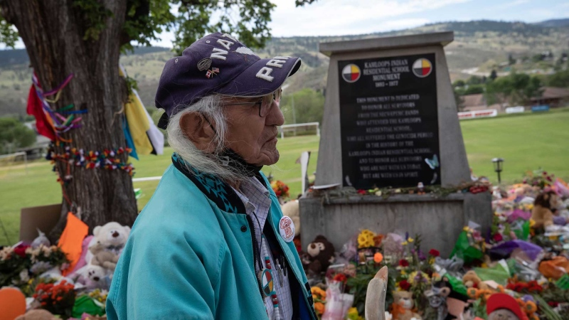 Kamloops Indian Residential School survivor Stanley Paul, 75, who was forced into the school when he was 7 and escaped by running away to the United States when he was 16, pauses at a growing makeshift memorial at a monument outside the former school, in Kamloops, B.C., on Friday, June 4, 2021. THE CANADIAN PRESS/Darryl Dyck
