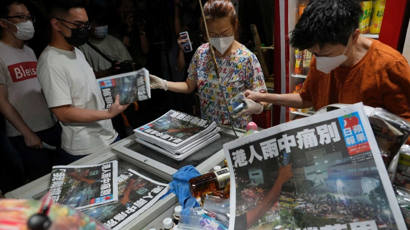 People queue up at a newspaper booth to buy last copy of Apple Daily in Hong Kong, early Thursday, June 24, 2021. ( AP / Vincent Yu)