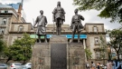 Pedestrians walk past the the African Memorial, dedicated to African military who died in the two World Wars, in downtown Nairobi, Kenya Thursday, April 22, 2021. (AP Photo/Brian Inganga)