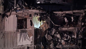 A light glows in a partially collapsed building early Thursday, June 24, 2021, in Surfside area of Miami, Fla. A partial building collapse in Miami caused a massive response early Thursday from Miami Dade Fire Rescue, according to a tweet from the department's account. Miami Dade Fire Rescue is conducting search and rescue. Authorities had no word yet on casualties, or details of how many people lived in the building. (AP Photo/Wilfredo Lee)