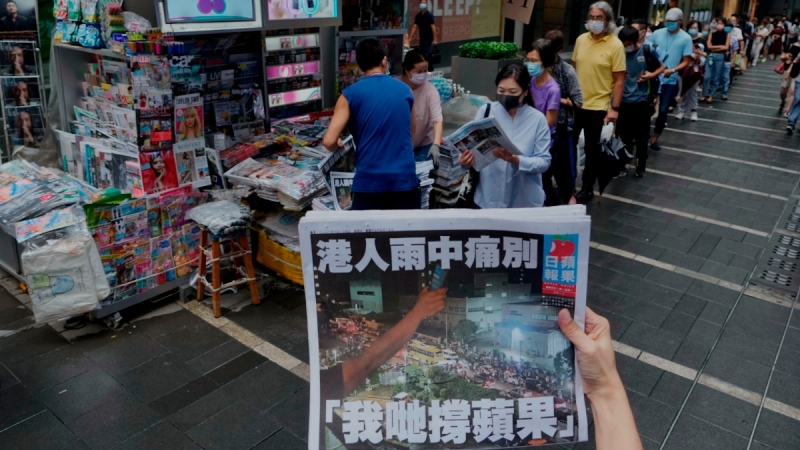 A woman tries to take a picture of last issue of Apple Daily in front of a newspaper booth in Hong Kong, on June 24, 2021. (Vincent Yu / AP)