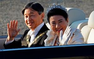 Japan's Emperor Naruhito, left, and Empress Masako, wave during a royal motorcade in Tokyo, on Nov. 10, 2019.  (Eugene Hoshiko / AP)