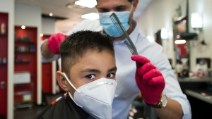 Five-year-old Aaren Tulsani gets his hair cut by owner and head barber Yasser Abbas, back, at Mohamad's Barber Shop during the COVID-19 pandemic in Cambridge, Ont., on Friday, June 12, 2020. THE CANADIAN PRESS/Nathan Denette