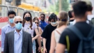 People wear face masks as they walk along a street in Montreal, Sunday, June 13, 2021, as the COVID-19 pandemic continues in Canada and around the world. THE CANADIAN PRESS/Graham Hughes
