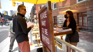 A server speaks to a patron as they arrive at an outdoor patio in Ottawa on the first day of Ontario's first phase of re-opening amidst the third wave of the COVID-19 pandemic, on Friday, June 11, 2021. THE CANADIAN PRESS/Justin Tang