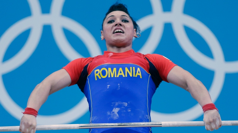 In this file photo dated Wednesday, Aug. 1, 2012, Romania's Roxana Cocos competes during the women's 69-kg weightlifting competition at the 2012 Summer Olympics, in London. A culture of alleged corruption among international weightlifting officials has been detailed in a 50-page investigative report released Thursday June 24, 2021, of covered-up doping cases, with Cocos stripped of her medal years later when re-tests revealed her steroid use.(AP Photo/Hassan Ammar, FILE)