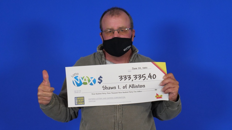Shawn Irvin, a potato farmer in Alliston, Ont. hold his big cheque from OLG after winning in the June 11, 2021, draw. (OLG)