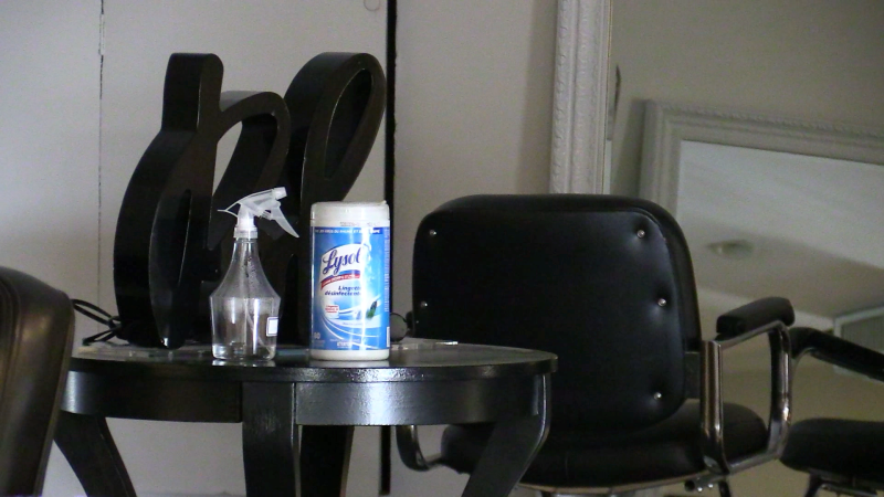 An empty chair and container of disinfectant are pictured inside a Barrie, Ont. hair salon on Thurs. June 24, 2021 (Mike Arsalides/CTV News)