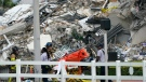 Miami-Dade Fire Rescue personnel walk with an empty stretcher past the scene where a wing of a 12-story beachfront condo building collapsed, Thursday, June 24, 2021, in the Surfside area of Miami. (AP / Lynne Sladky)