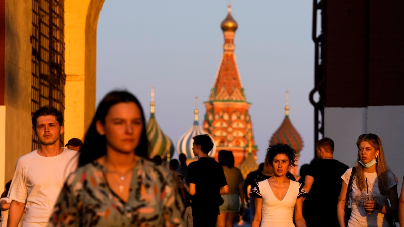 People, most of them without face masks, walk at Red Square during sunset in Moscow, Russia, Thursday, June 24, 2021. (AP Photo/Alexander Zemlianichenko)