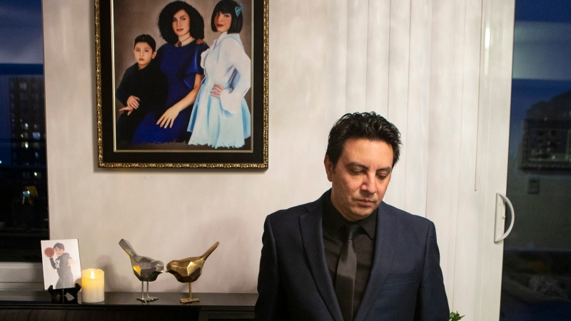 Alireza Ghandchi is photographed in front of a portrait of his wife Faezeh, daughter Dorsa and son Daniel in Richmond Hill, Ont., Friday, January 1, 2021. (THE CANADIAN PRESS/Chris Young)