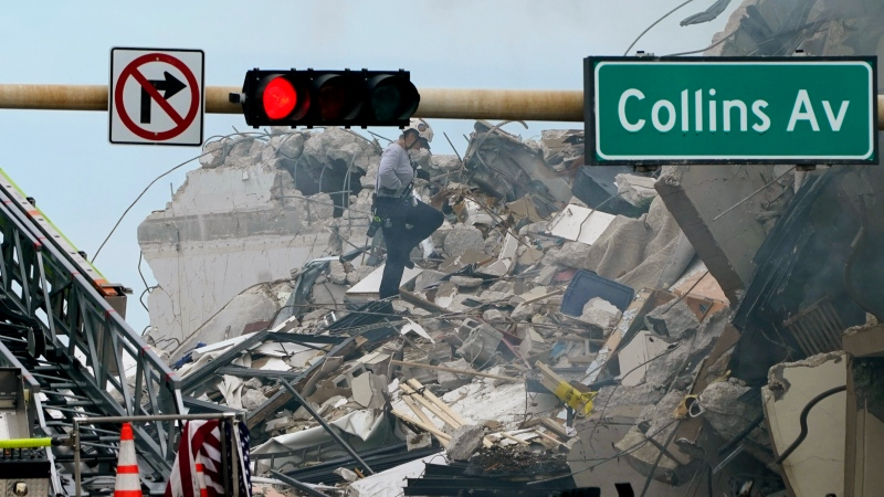 A rescue worker walks among the rubble where a wing of a 12-story beachfront condo building collapsed, Thursday, June 24, 2021, in the Surfside area of Miami. (AP Photo/Lynne Sladky)