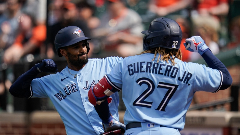 Toronto Blue Jays' Marcus Semien, left, celebrates his solo home run off Baltimore Orioles starting pitcher Dean Kremer with Vladimir Guerrero Jr. (27) during the first inning of a baseball game, Saturday, June 19, 2021, in Baltimore. (AP Photo/Julio Cortez)