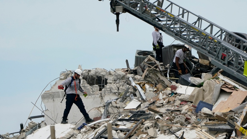 Rescue worker walk among the rubble where a wing of a 12-story beachfront condo building collapsed, Thursday, June 24, 2021, in the Surfside area of Miami. (AP Photo/Lynne Sladky)