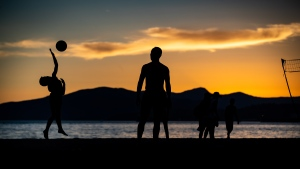 A young boy is silhouetted while playing volleyball at English Bay Beach at sunset, in Vancouver, B.C., on Monday, June 21, 2021. THE CANADIAN PRESS/Darryl Dyck