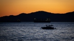 People are silhouetted on a boat on English Bay at sunset, in Vancouver, B.C., on Monday, June 21, 2021. THE CANADIAN PRESS/Darryl Dyck