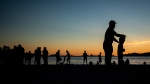 People are silhouetted at English Bay Beach at sunset, in Vancouver, B.C., on Monday, June 21, 2021. THE CANADIAN PRESS/Darryl Dyck