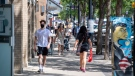 People walk, some with masks and some without, in downtown in Saskatoon, Sask., Friday, June 25, 2021. All public health restrictions, including the mask mandate and gathering limits, will be lifted in Saskatchewan on July 11. THE CANADIAN PRESS/Liam Richards