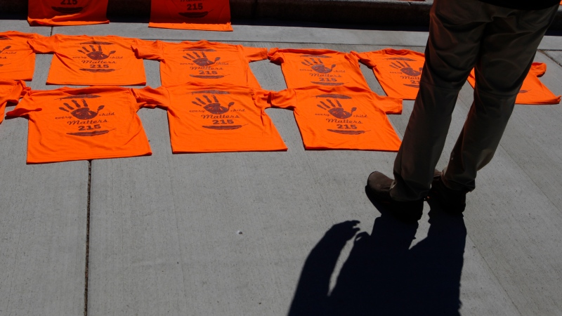 A man looks over the orange shirts, shoes, flowers and messages are displayed on the steps outside the legislature in Victoria, B.C., on Tuesday, June 8, 2021. (THE CANADIAN PRESS / Chad Hipolito)