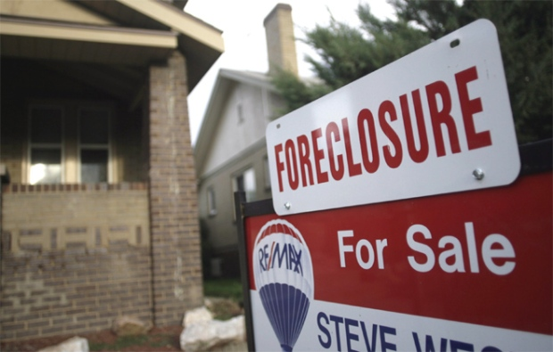 A foreclosure sign tops a sale sign outside an existing home on the market in northwest Denver on Aug. 29, 2007.  (AP / David Zalubowski)