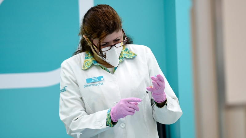Pharmacist Zaineb Hassan draws up a dose of COVID-19 vaccine that she will administer to Prime Minister Justin Trudeau at a pharmacy in Ottawa, Friday, July 2, 2021. (Justin Tang /THE CANADIAN PRESS)